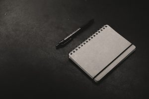 pen and a blank notebook on a table